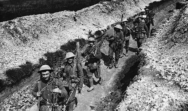 Equipped British soldiers in a trench looking at the camera