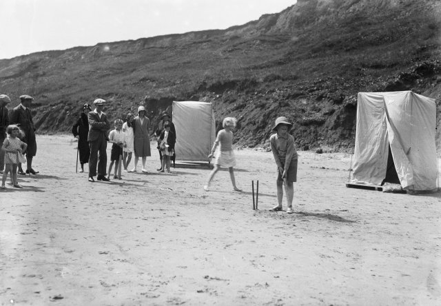 Family plays cricket on the beach