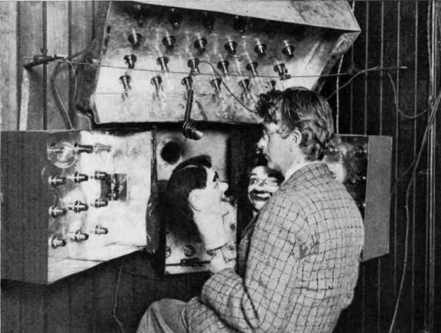 John Logie Baird with two ventriloquist's dummy heads – 'Stooky Bill' to the right and 'James' to the left - that he used in an early demonstration of his television system, 25 March 1925, at London's Selfridges. Image in the public domain.
