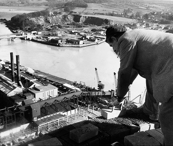 Bricklayer at work on top of a chimney during the construction of Plymouth Power Station,