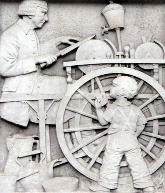 One of five enormous window-height reliefs - sitting between the first floor windows of Buchanan House, St James's Square - depicting a knife-grinder at work watched by a child.