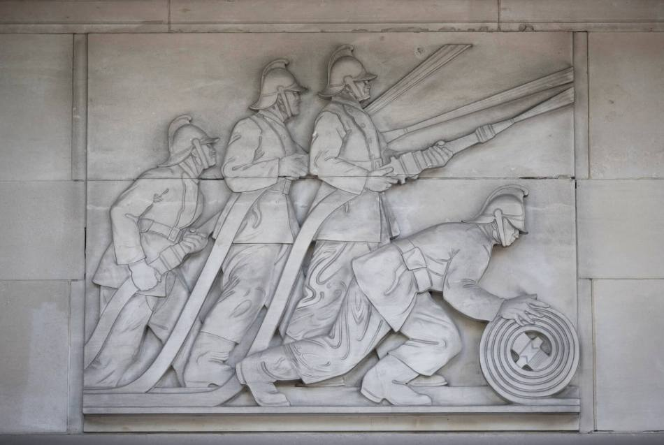 Detail of stone relief of firemen in action by sculptor Stanley Nicholson Babb on the exterior of Lambeth Fire Station