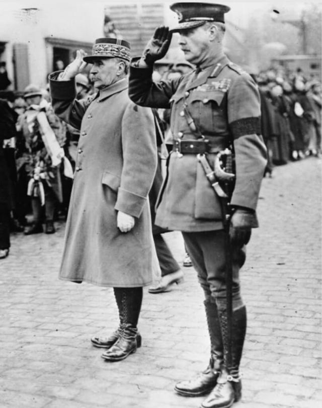 Black and white photo of two men standing and saluting with crowds of civilians onlookers behind.