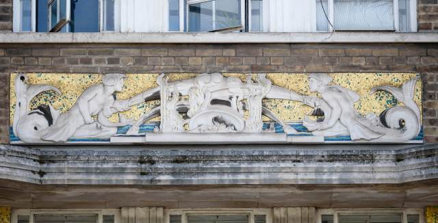 Two mermen with fish 'hoses' extinguish a stylised fire. First floor carved relief