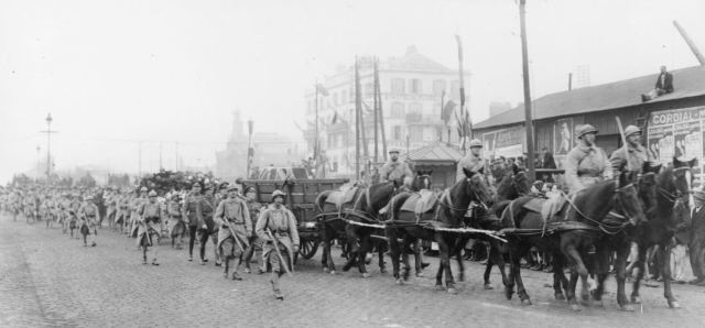 A carriage bearing the Unkown Warrior's coffin, drawn by 6 horses and accompanied by an escort of French soldiers, forms a ceremonial procession.