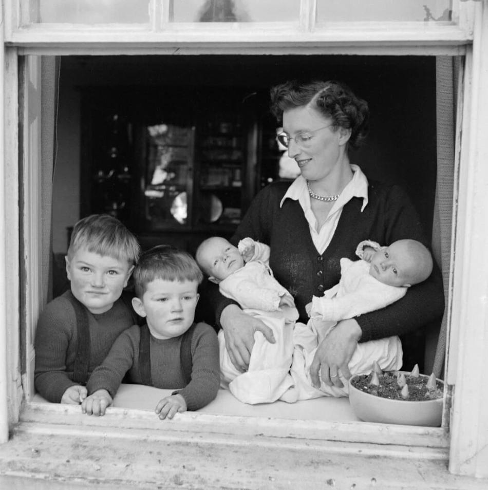 An informal portrait of a family at an open window at mundenbury, great munden, showing two young boys and a woman holding twin babies.