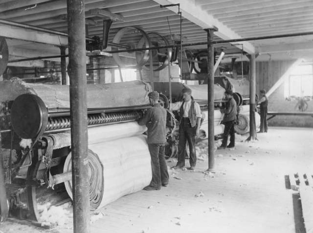 A group of factory workers operating the gig milling machine