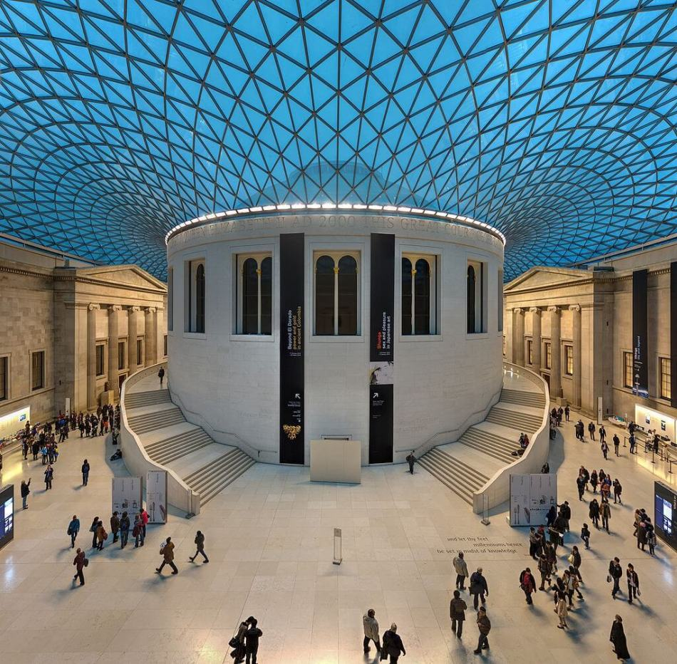A wide shot of the British Museum's large entrance hall, which has a expansive cross-hatched glass ceiling.