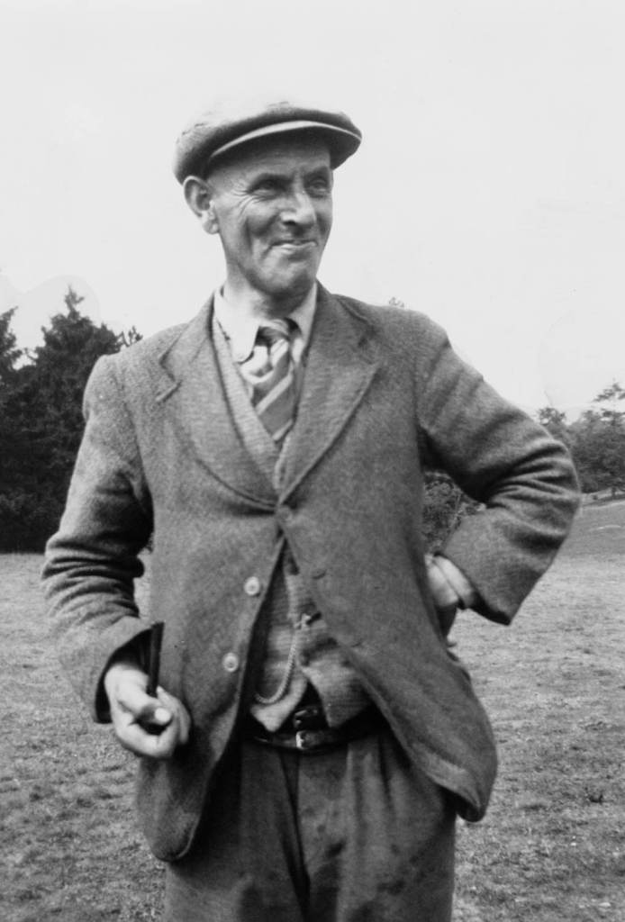 Black and white archive portrait of a man wearing inter-war clothing carrying a pipe.