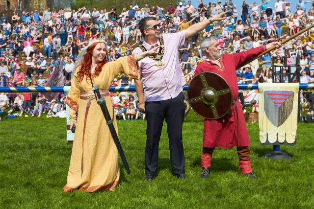 A civic dignitary taking part in pageant with costumed re-enactors depicting Athelflaed and a Saxon warrior.