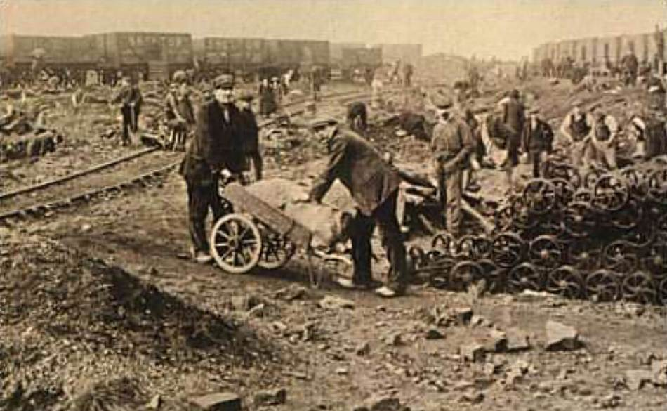 Two men foraging for coal, with men in the background