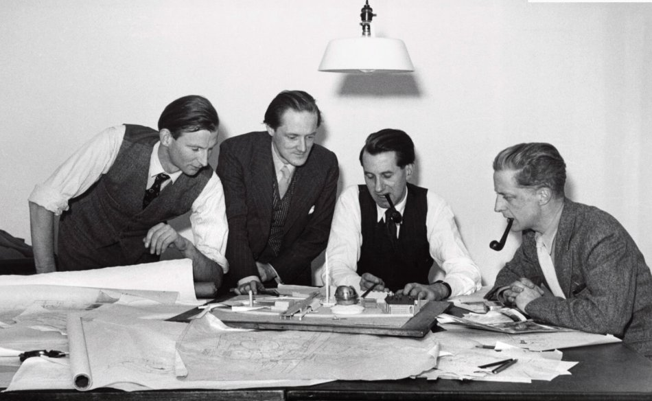 Four of the Festival co-ordinators, two with pipes, examine a model of the Festival site, on a desk covered with maps.