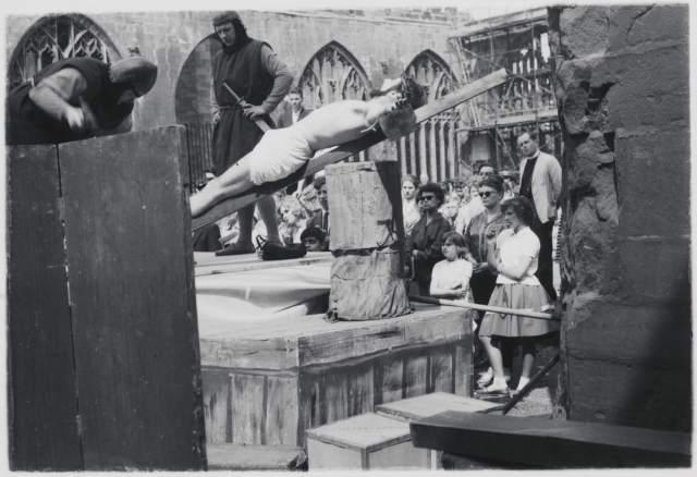 Spectators watch actors in a scene depicting Christ's Crucifixion