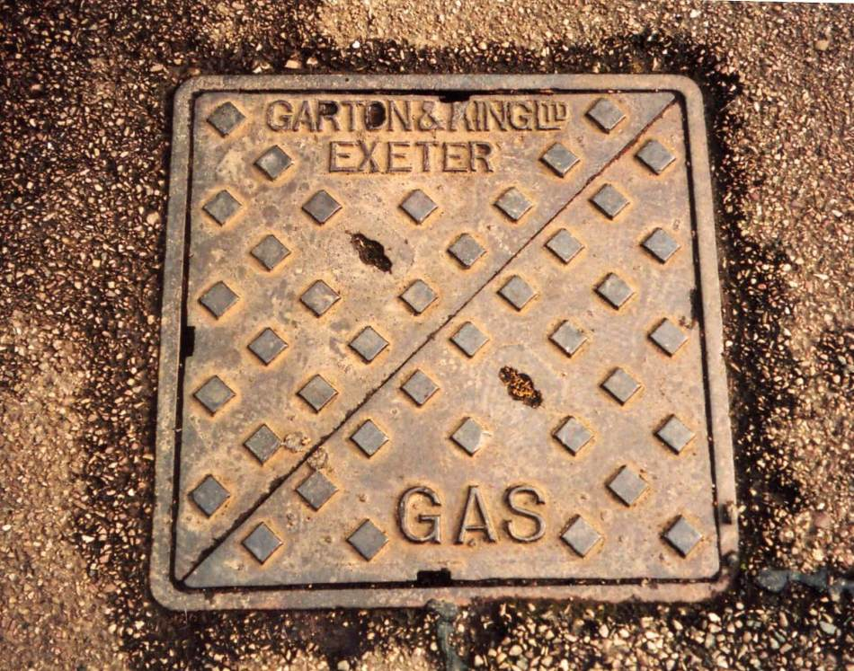 Square manhole cover with 'Exeter Gas' text and a diagonal line.