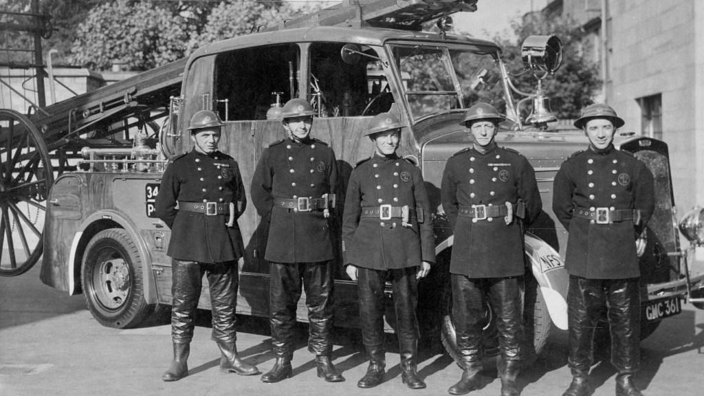 Five firemen stand in front of the pump vehicle.