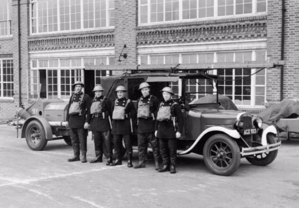 Five men in uniform stand by their firefighting vehicle.