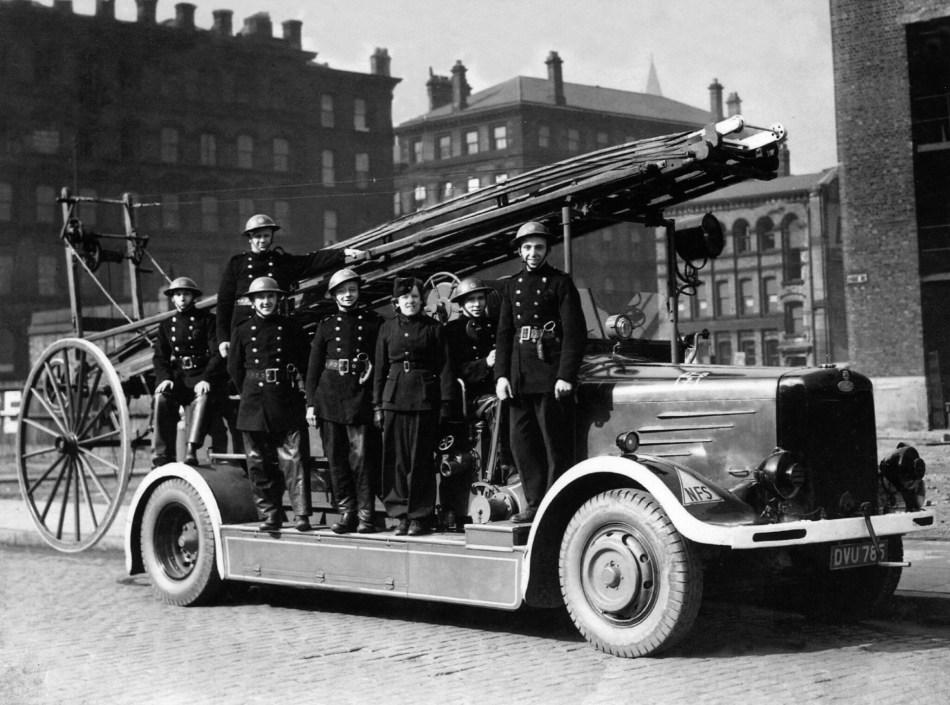 Firemen and firewomen pose on a pump.