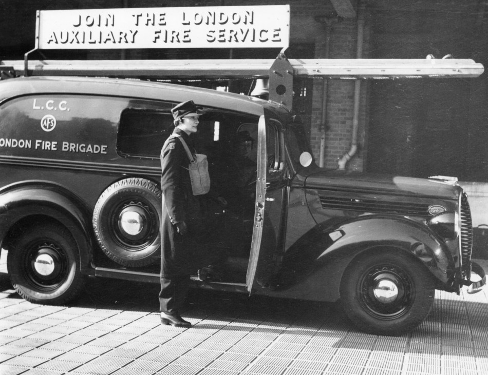 A woman in uniform stands by a recruitment van with London Fire Brigade on the side.