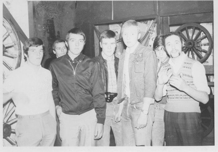 A group of  young male clubbers inside a club decorated with wheel motifs.