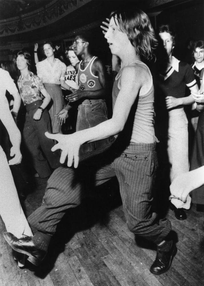 A group of young dancers in a club wearing 1970s clothing typical of the Northern Soul scene such as a sleeveless tops and wide legged Oxford bags trousers.