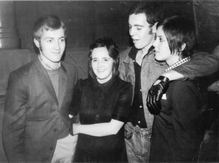 Two young couples in smart and smart casual clothing worn around 1969-70, one young man wears a driving glove on one hand.