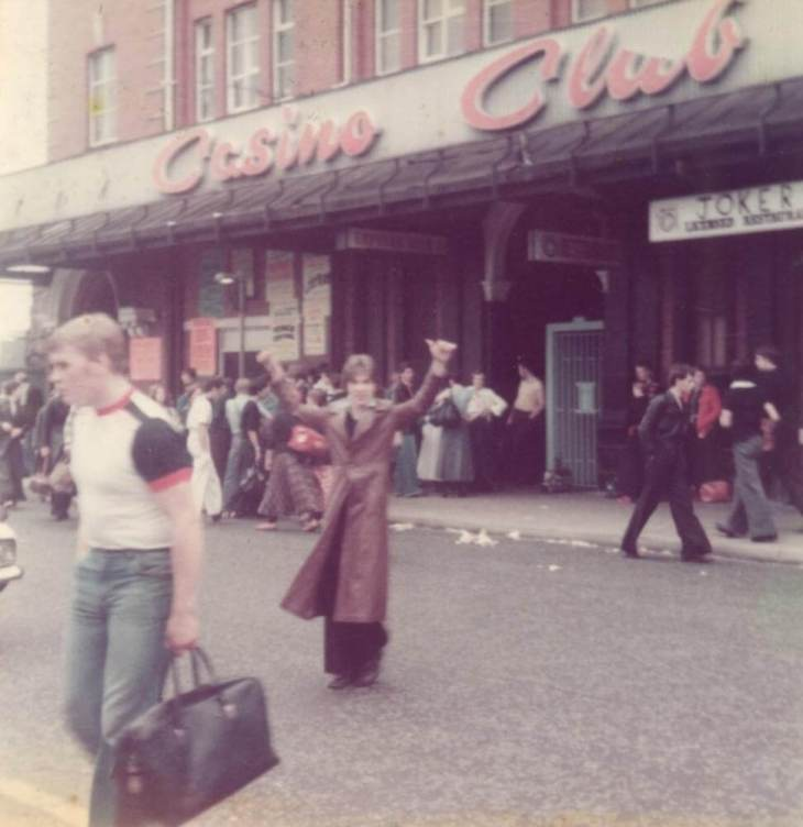 Clubbers in 1970s clothing outside a dance venue, the club signbears the name the name 'Wigan Casino'.