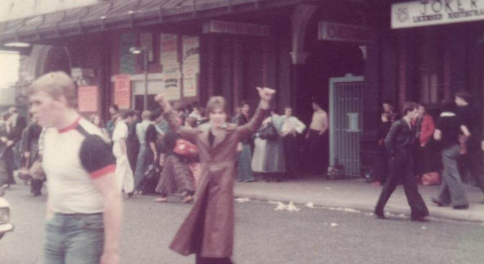 Club goers outside a dance venue in1970s clothing.