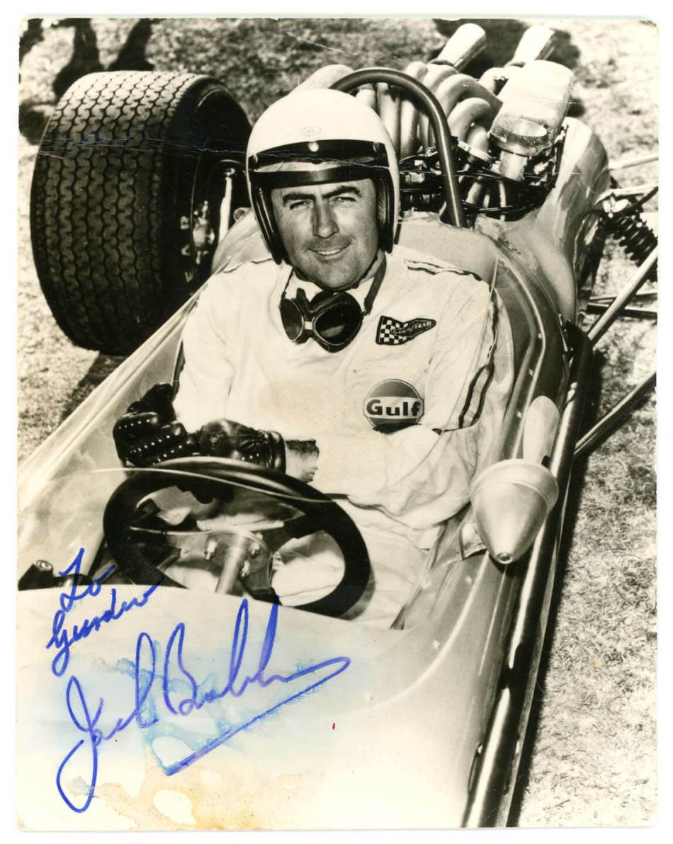 Man in F1 car, with signed message 'To Gurdev, Jack Brabham,