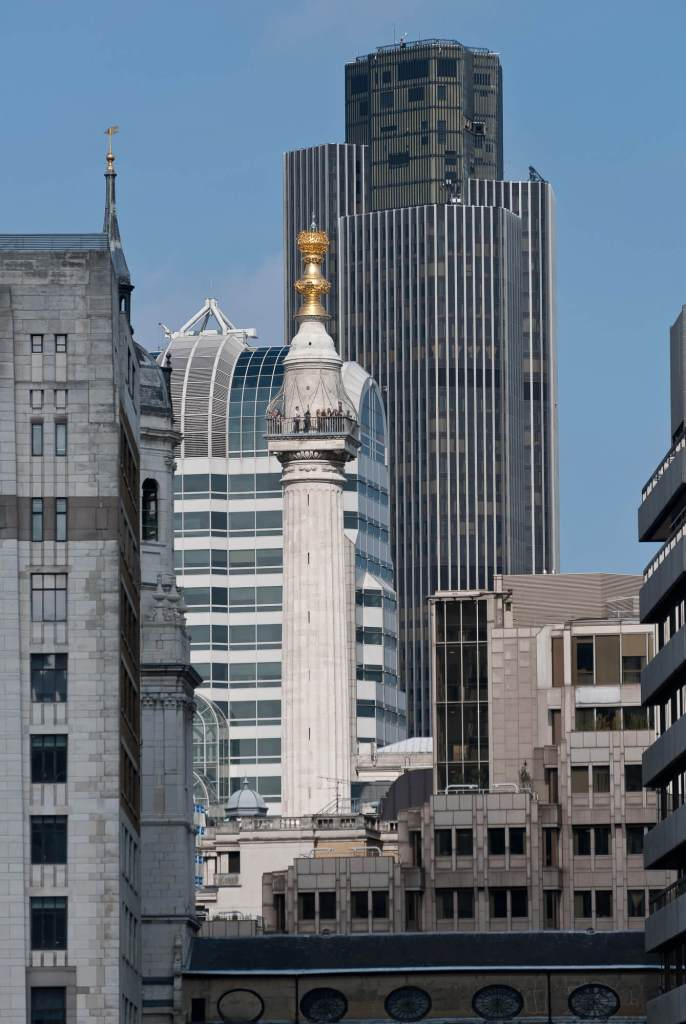The Monument is a tall white doric column topped with a gilded urn of fire, surrounded by buildings.