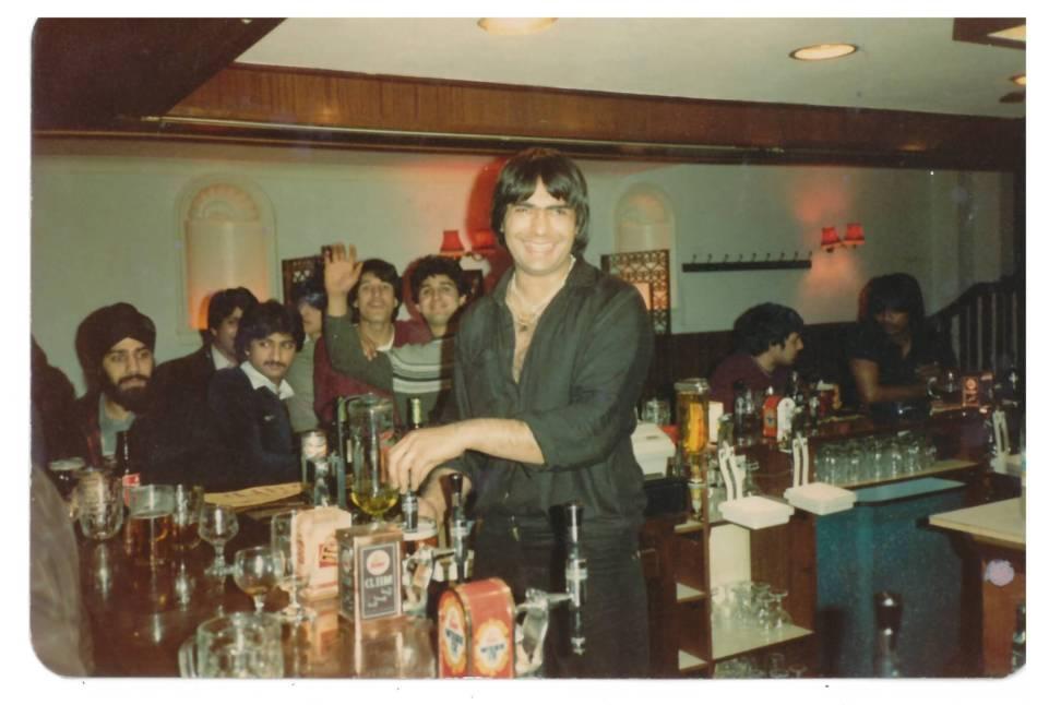 Man smiles behind a bar with men waving behind him.