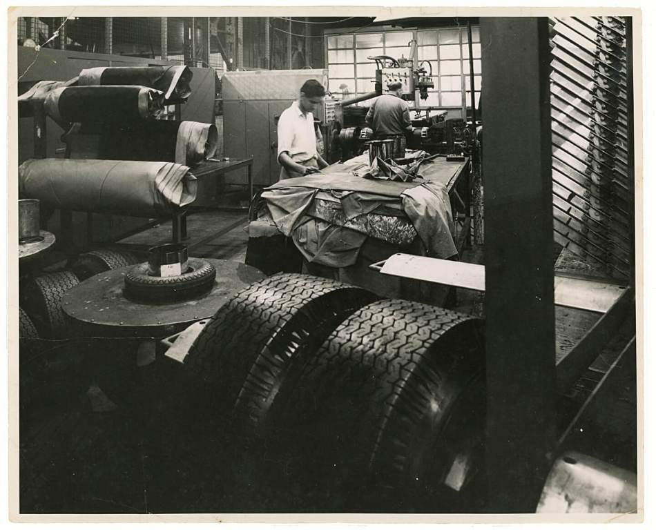 A man works in a factory surrounded by large tyres.