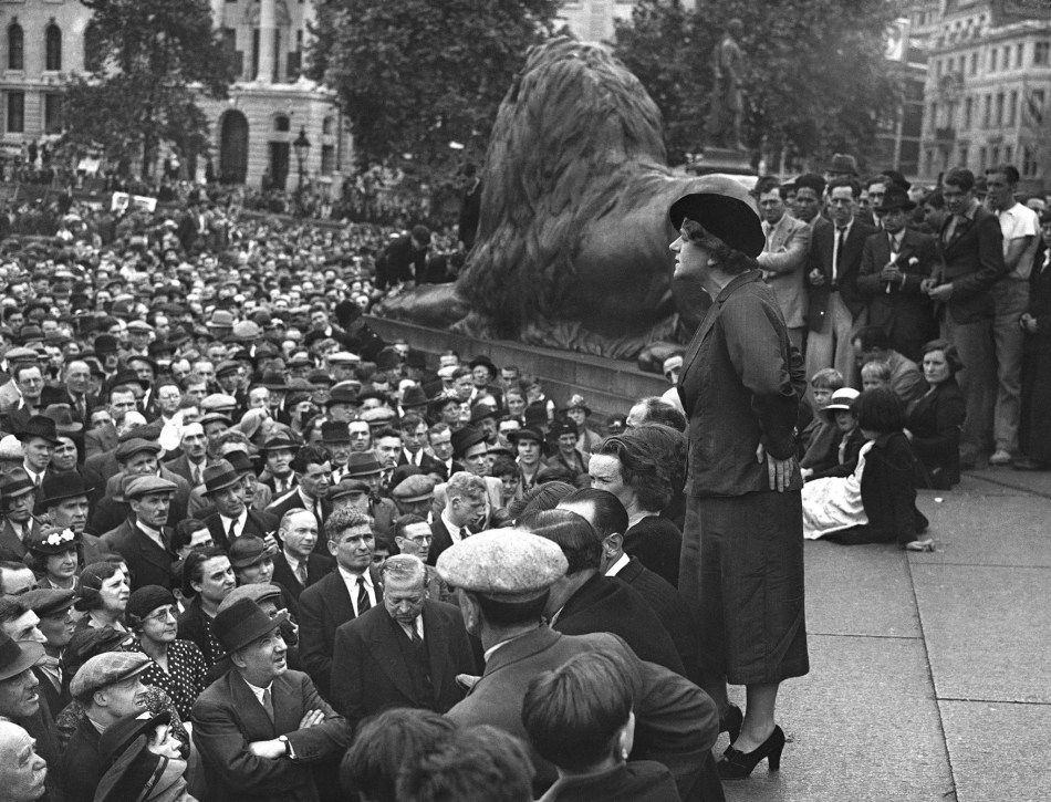 A well-dressed woman speaks to a huge group of men and women, in Trafalgar square. A statue of a lion is behind her.