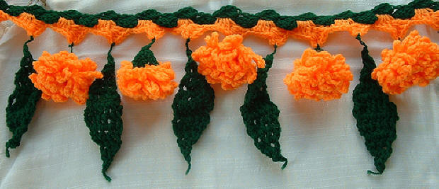 Knitted toran simulating marigolds and mango leaves