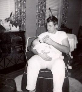 1954- Edward A. McMurray, Jr., feeding daughter.