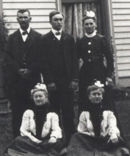 William Edward Roberts Family, 1900. Standing, from left: W. E. Roberts, son Orville Roberts, Orville's mother, Mary M. (Main) Roberts. Seated on the ground in front of them are Maude Roberts & Clara Roberts, with Maude possibly having the lighter hair as seen in the 1892 photo. Cropped from a larger family photo.