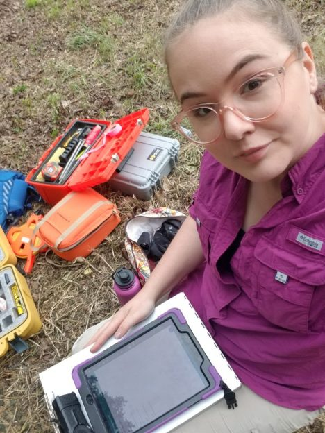 Kate using digital tablet to collect data in the field, boxes of excavation and remote sensing equipment in the background