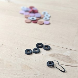 Black stitch markers being made