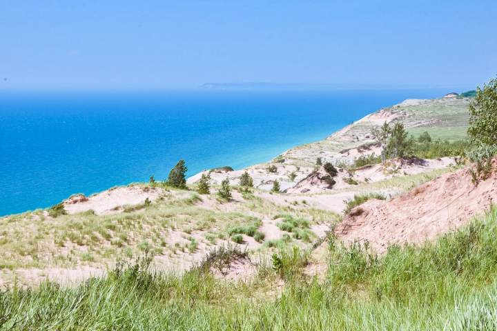 Lake Michigan Overlook Sleeping Bear Dunes National Lakeshore hiking trail along the water through the dunes. | herlifeadventures.blog | #camping #usdestinations #sleepingbeardunes #nationallakeshore #travelhacks #travelguide #adventuretravel #roadtrip #nationalpark #nationalparkroadtrip #michigantravel #greatlakes #ustravel #summer #bucketlist