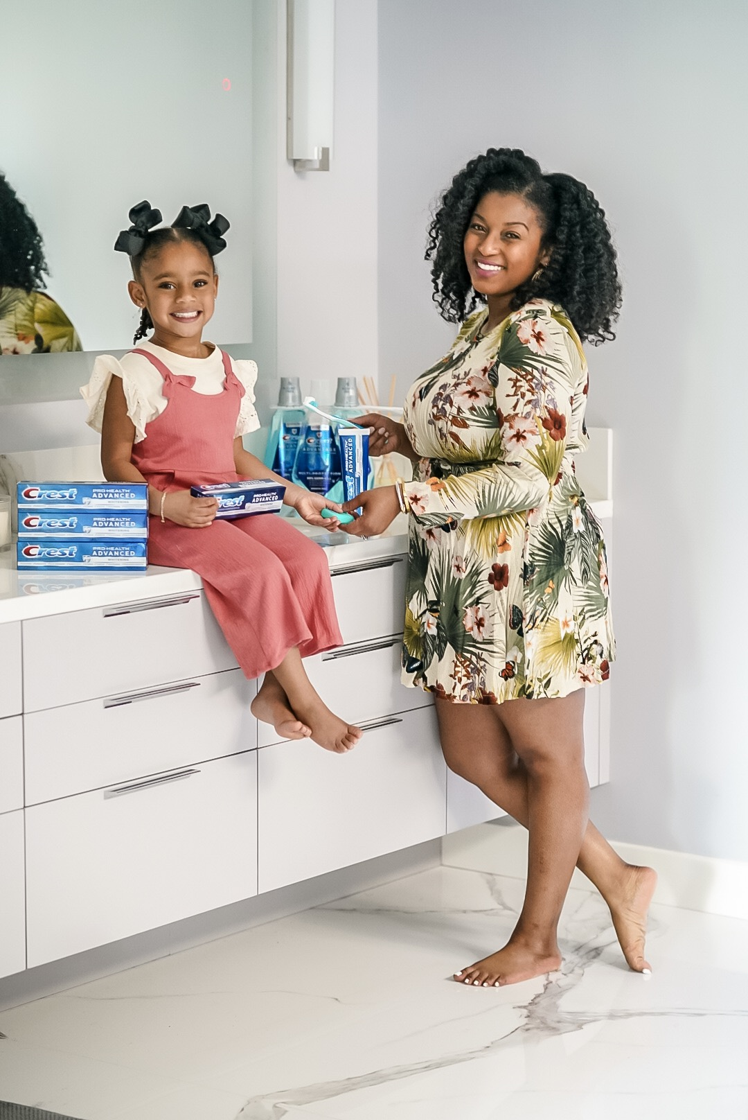 mother and daughter discussing whether you should brush or floss first using Crest products.