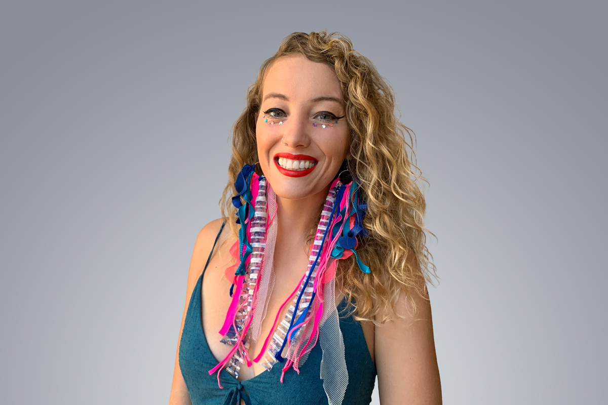 Heroic Headshot on grey background of woman in colorful clothes taking remote virtual headshot.