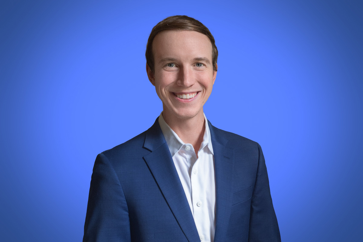 Heroic Headshot on blue background of business man in suit taking remote virtual headshot