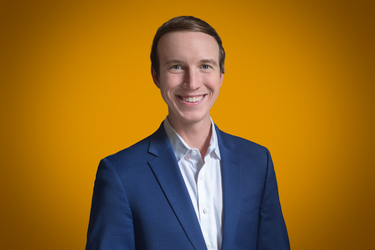 Heroic Headshot on orange background of business man in suit taking remote virtual headshot
