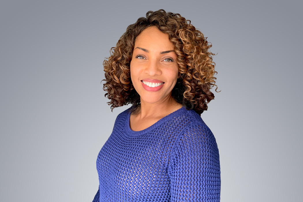 Heroic Headshot on grey background of business casual woman taking remote virtual headshot.