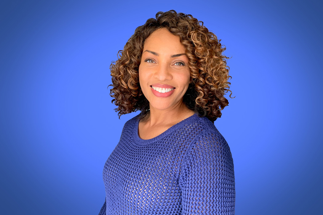 Heroic Headshot on blue background of business casual woman taking remote virtual headshot.