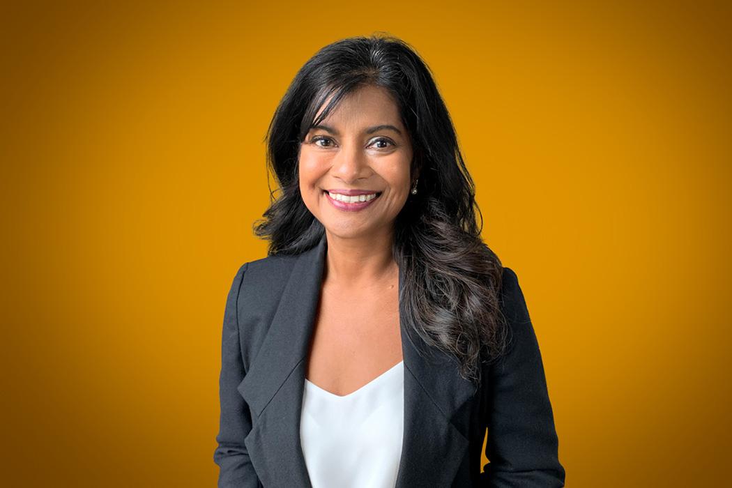 Heroic Headshot on orange background of business woman in suit jacket taking remote virtual headshot.