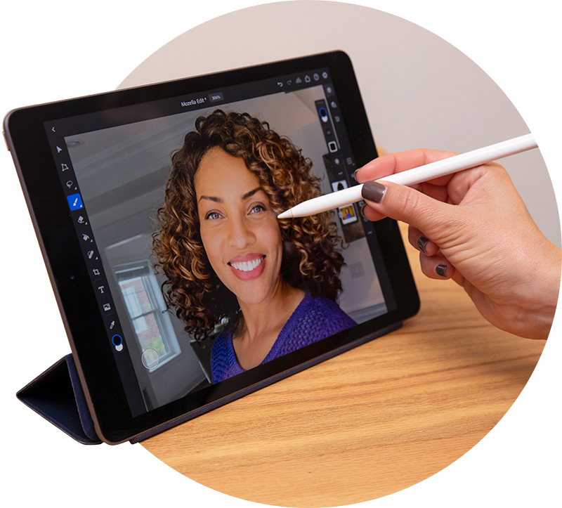 A close up image of the hand of a world-class professional photo editor retouching a Heroic Headshot with a stylus pen and tablet using high-quality headshot retouching software.