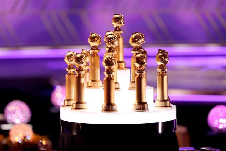Golden Globes Statues with purple background and lightened up pyramid-shaped stand
