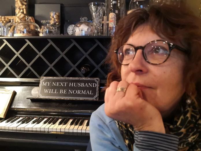 In einem Cafe in Riga, Lettland. Tini_nachdenklich mit Spruch im Hintergrund: MY NEXT HUSBAND WILL BE NORMAL