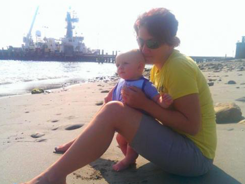 Ivona Cetinić sits with son Veles on a Rhode Island beach after her four-week research cruise aboard R/V Endeavor (in background) in summer 2014. Photo Credit: Via UMaine.edu