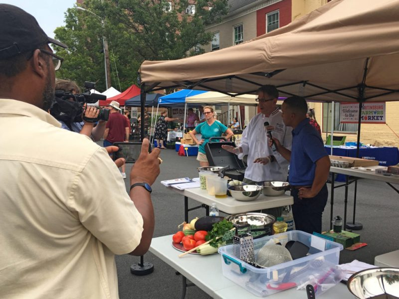 Chef Steve Weiss showing market-goers how to make eggplant bruschetta while being interviewed by the local news stations.